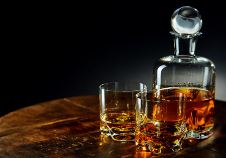 Photo pour Decanter of whiskey besides two glasses half filled on a round wooden table in a dark room - image libre de droit