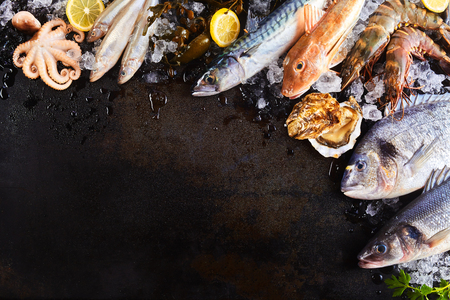 Foto de High Angle Still Life View of Variety of Raw Fish and Seafood Chilling on Ice with Lemon and Arranged Around Border of Image on Rustic Wooden Table Surface with Copy Space - Imagen libre de derechos