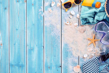 Photo pour Summer vacation water sports background theme with seashells, loose sand, sunglasses, swimming clothes and underwater goggles over weathered wood blue background with copy space - image libre de droit