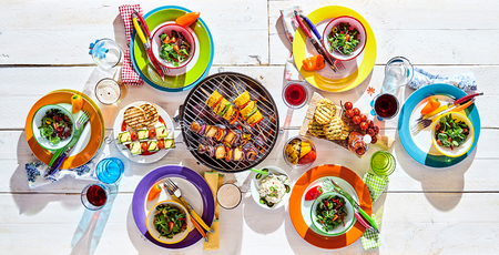 Photo pour Overhead view of a colorful picnic table laid with multicolored plates, salad beverages and a BBQ with tofu kebabs for healthy vegetarian or vegan cuisine - image libre de droit