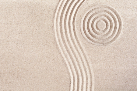 Photo pour Natural flowing wave form and concentric circles raked in the smooth sand in a Japanese Zen Garden portraying tranquility and meditation in a wellness concept - image libre de droit
