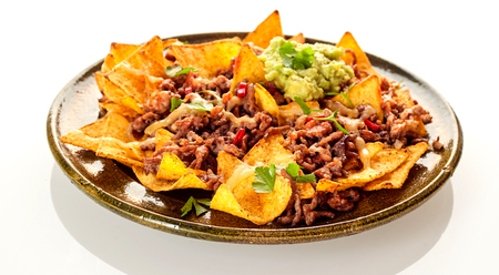 Round ceramic plate with crunchy yellow corn tortilla chips, cheese and beef over white background with soft set down shadow