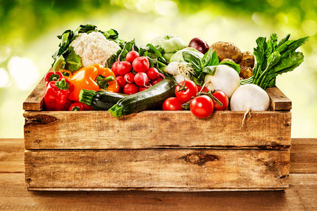 Photo pour Wooden crate of farm fresh vegetables with cauliflower, tomatoes, zucchini, turnips and colorful sweet bell peppers on a wooden table outdoors in sparkling sunlight on greenery - image libre de droit
