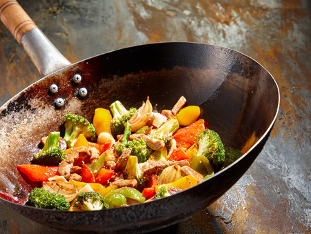 Foto de Tasty vegetable dish with broccoli and colorful peppers cooked in oil stained asian wok recipe against a rustic background - Imagen libre de derechos