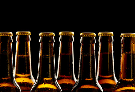 Photo pour Row of chilled unopened brown beer bottles in a close up view of the necks and tops over a black background conceptual of Oktoberfest - image libre de droit