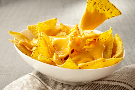 Single triangular yellow corn tortilla chip pulled out of bowl of cheese covered nachos over gray and white tablecloth