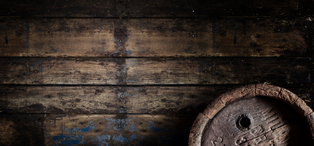 Foto de Old oak beer, wine or brandy barrel over a weathered textured wooden wall in a cellar or tavern in panoramic banner format with copy space - Imagen libre de derechos