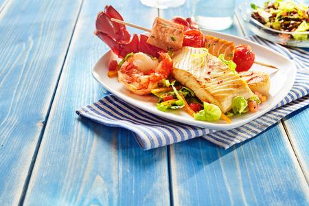 Foto de Fresh seafood snack salad on square plate over blue wooden table with copy space - Imagen libre de derechos
