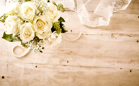 Foto de High Angle Still Life of Bridal Bouquet with Delicate White Roses and Greenery on Rustic Wooden Table with Feminine Lace Veil and Copy Space - Imagen libre de derechos