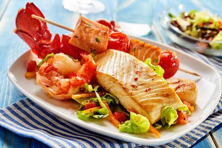 Foto de Arrangement of seafood appetizers on rectangular plate. Includes shrimp, lobster and fish meat on skewer with vegetables. - Imagen libre de derechos