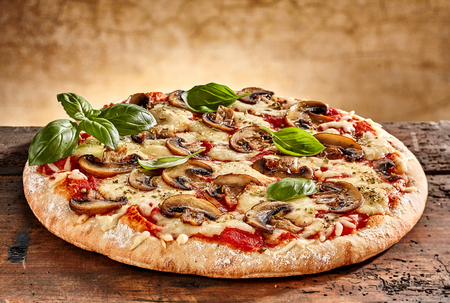 Close up on delicious freshly baked small pizza with melted cheese mushrooms and basil
