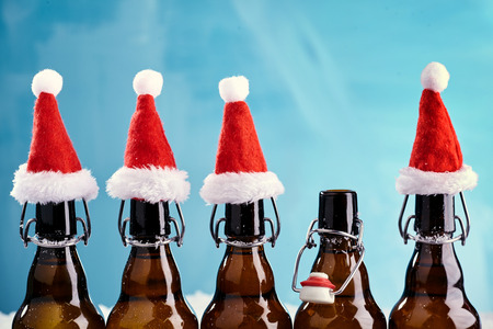Photo for Winter beer bottle merry christmas party. Beer Bottles in a row with funny christmas hats for xams happenings - Royalty Free Image
