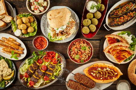Photo for Top down view on freshly prepared delicious varieties of Mediterranean dishes on wooden table - Royalty Free Image