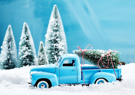 Old blue vintage toy truck with a Christmas tree loaded on the back driving through thick snow in a winter forest in a seasonal still life scene