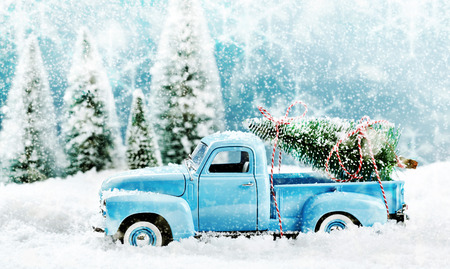 Photo for Vintage toy truck fetching a Christmas tree from a pine forest in a winter snow storm driving through thick snow with a tree loaded on the back, side view seasonal still life - Royalty Free Image