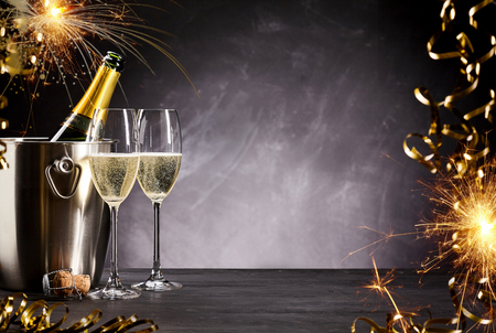 Romantic celebration with sparklers, party streamers and flutes of champagne alongside a bottle on ice with a smoky atmospheric background and copyspace