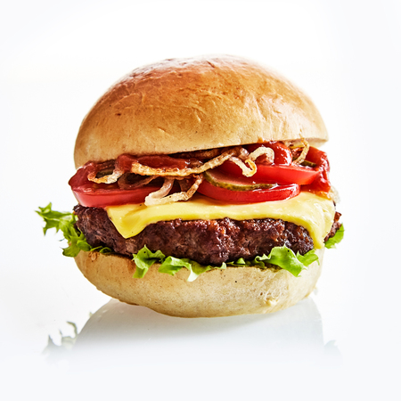 Close up of thick and juicy cheese burger on a plain bun with leafy green lettuce