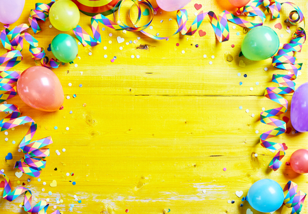Foto de Bright colorful carnival or party frame of balloons, streamers and confetti on a rustic yellow wood table with central copy space for your greeting , invitation or advertising - Imagen libre de derechos