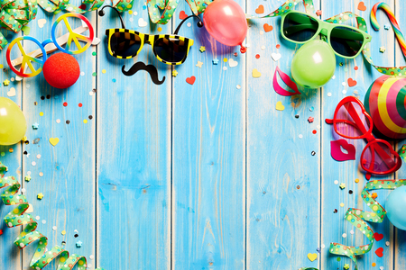 Carnival frame with colorful costume accessories in the form of fun shaped sunglasses, a party hat and coiled streamers on a blue wood background with copy space