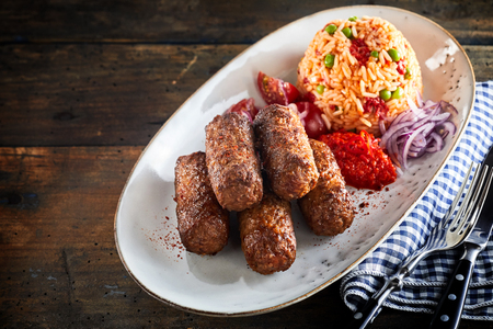 Traditional cevapcici, or rolled ground beef patties, served with savory rice on a long oval platter on rustic wood
