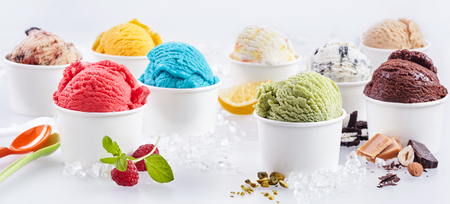 Photo pour Large selection of artisanal takeaway ice cream in tubs each with the fresh ingredients alongside including raspberry, pistachio, bubblegum, caramel, chocolate, hazelnut and lemon - image libre de droit