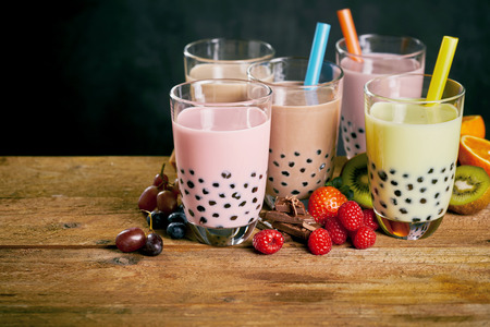 Photo pour Assortment of milky bubble teas with fresh fruit ingredients served with wide straws on a wooden table with copy space - image libre de droit