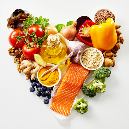 Foto de Heart-shaped still life of healthy food for the heart and cardiovascular system with fresh ingredients rich in antioxidants and omega-3 fatty acids viewed from above isolated on white - Imagen libre de derechos