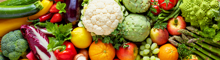 Foto de Panoramic wide organic food background concept with full frame pile of fresh vegetables and fruits mix forming bright colorful image - Imagen libre de derechos