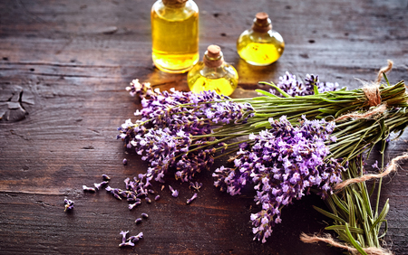 Photo pour Bunches of fresh lavender with three small bottles of essential oil or extract for aromatherapy or alternative medicine lying on rustic wood with copy space - image libre de droit