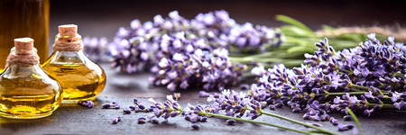 Panoramic banner or header of fresh purple lavender with flacons of essential oil for aromatherapy, alternate medicine and perfumery