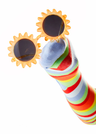 Happy colorful sock puppet wearing sunglasses isolated on white background