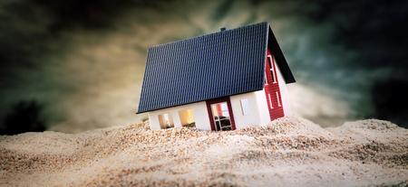 Foto de Miniature of house standing in pile of sand - Imagen libre de derechos