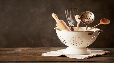 Strainer full of kitchen utensils standing on dishcloth