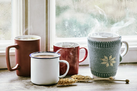 Four steaming hot cups of tea brewing on a bright morning window sill.