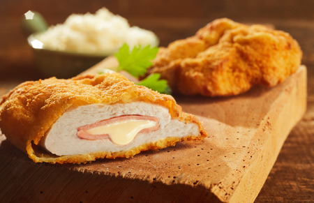 Fried cordon bleu pork served on wooden cutting board