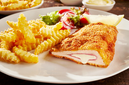 Piece of fried cordon bleu chicken served with french fries and salad on plate