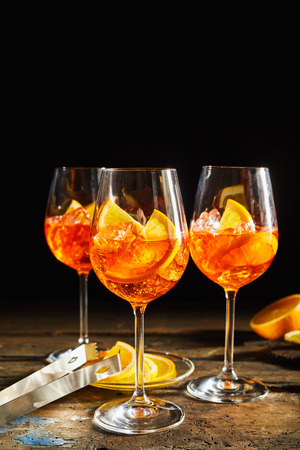 Photo pour Refreshing lemon spritz cocktails on rustic, dark timber background with sliced lemon. - image libre de droit