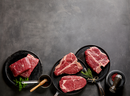 Foto de Raw steaks and frying pans with seasoning, garnishes and ingredients on a dark rustic background with copy space. - Imagen libre de derechos
