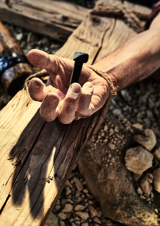 Photo for Reenactment of Jesus Christ crucifixion with human hand nailed to wooden cross in close up - Royalty Free Image