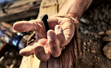 Photo for Hand of Christ nailed to the cross with a close up view of a mans hand with an iron nail hammered through onto a wooden cross symbolic of the crucifixion of Christ at Easter - Royalty Free Image