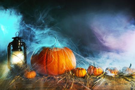 Photo pour Halloween theme with pumpkins under spider web with vintage lamp against smoky dark background - image libre de droit