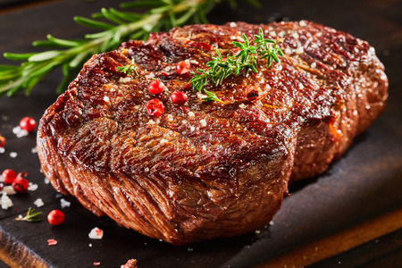 Photo for Piece of roast beef with spices served on wooden cutting board - Royalty Free Image