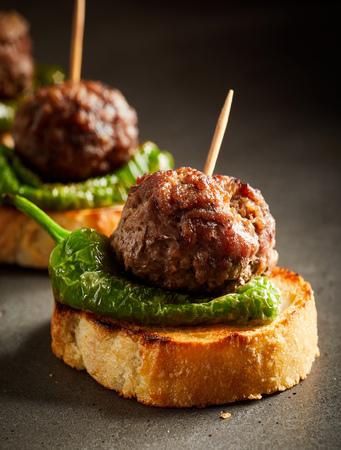 Foto de Roasted meatballs with green pepper served on slice of baked bread - Imagen libre de derechos