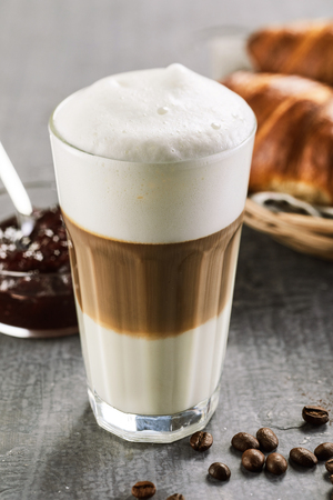 Glass of macchiato coffee with thick milk foam standing on table in close up view