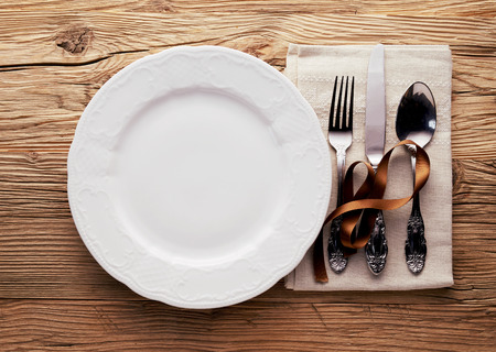 Foto de Simple Christmas place setting with utensils and a napkin decorated with a brown ribbon alongside a generic empty white plate on a wood table - Imagen libre de derechos