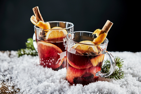 Tasty mulled red wine, or Gluhwein, with orange and cinnamon served in glasses on a bed of winter snow to celebrate the Christmas season