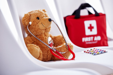 Foto de Medical concept of teddy bear with stethoscope sitting on chair with first aid kit in background - Imagen libre de derechos