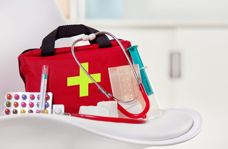 Foto de Close-up of a first aid kit next to colorful pills, syringe, stethoscope and sterile bandages on a white chair in a medical center - Imagen libre de derechos