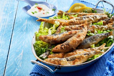 Foto de Healthy Mediterranean or Greek appetizer of fried sardines in batter on a bed of fresh lettuce served in a vintage dish over a blue wood background with copy space - Imagen libre de derechos