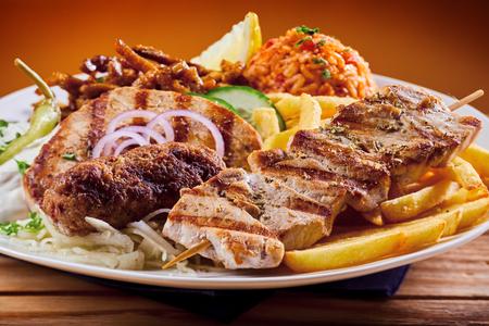 Photo pour Greek grill platter with souvlaki, souzuki steak and grilled pork skewers served with refreshing raiti yogurt dressing and pilaf - image libre de droit